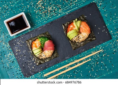 Sushi donuts on wooden board with ginger on black background