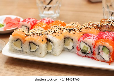 Sushi with fish, cheese and caviar on a white rectangular plate, empty glasses in the background