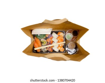 Sushi to go concept. Top view of takeaway box with sushi rolls and various sauce cups in brown paper bag. Isolated on white, studio shot.