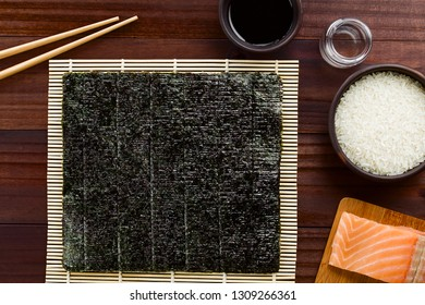 Sushi ingredients, nori seaweed on makisu bamboo mat for rolling, chopsticks, soy sauce, rice vinegar, raw sushi rice and fresh raw salmon on the side, photographed overhead