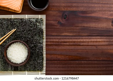 Sushi ingredients, nori seaweed, raw sushi rice and chopsticks on makisu bamboo mat, fresh raw salmon and soy sauce above, photographed overhead with copy space on the right side