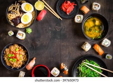 Sushi and japanese food on dark background. Sushi rolls, hiyashi wakame, miso soup, ramen, fried rice with vegetables, nigiri, soy sauce, chopsticks. Asian/Japanese food frame. Overhead