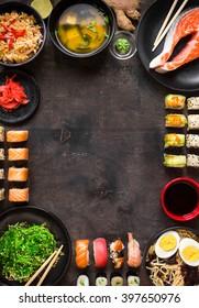 Sushi and japanese food on dark background. Sushi rolls, hiyashi wakame, miso soup, ramen, fried rice with vegetables, nigiri, salmon steak, chopsticks. Asian/Japanese food frame. Overhead