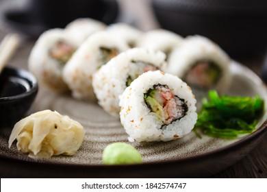 Sushi maki rollt Kalifornien mit Krabbe, Gurken und Avocado auf einem Teller mit Stäbchen, Sojasauce, Wespabi und Ingwer. Japanische traditionelle Meeresfrüchte werden zum Mittagessen im modernen Gourmet-Restaurant serviert.