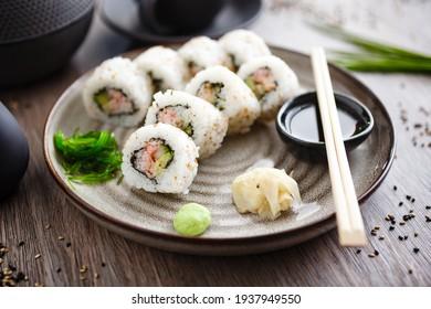 Sushi maki rollt Kalifornien mit Krabbe, Gurken und Avocado auf einem Teller mit Stäbchen, Sojasauce, Wespabi und Ingwer. Japanisch traditionelle Meeresfrüchte zum Mittagessen im modernen Gourmet-Restaurant