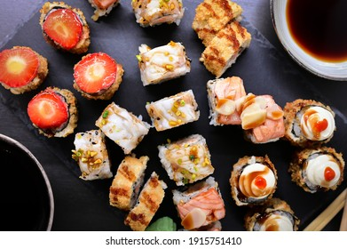 Sushi maki rolls on a stone plate. japanese food, Mix colorful sushi Set of different kinds of sushi rolls with salmon, shrimp and vegetables. On black rustic background. Top view.