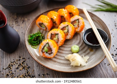 Sushi maki rolls with salmon, avocado, cucumber, flying fish roe on a plate with chopsticks, soy sauce, wasabi and ginger. Japanese traditional food served for lunch in modern gourmet restaurant.