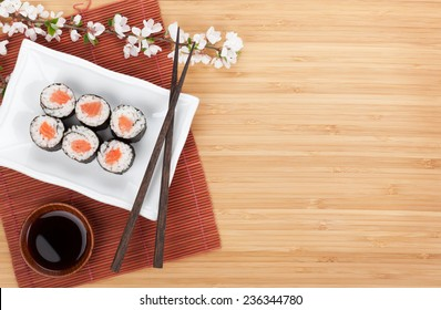 Sushi maki with salmon and sakura branch over bamboo table