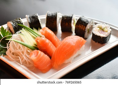 Sushi maki salmon set, white plate, dark background