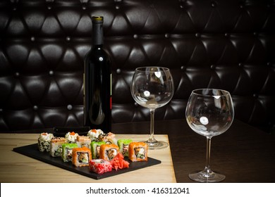 sushi mix served dinner with wine on table at restaurant, evening date in cosy room, food photography