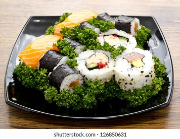 Sushi mixed in black plate on Japan wooden table