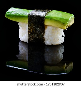 Sushi nigiri with avocado on black background with reflection. Japanese cuisine avocado nigiri sushi isolated. Japanese Nigiri sushi with avocado, rice and nori