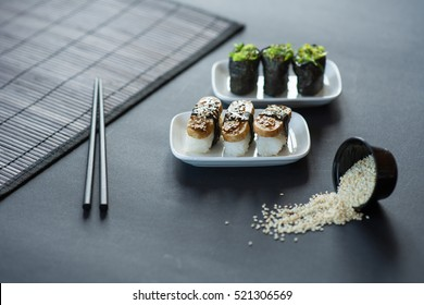 Sushi nigiri on black table in white plates
