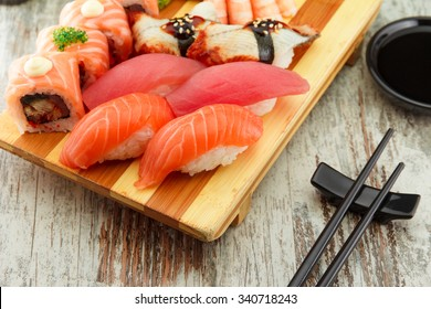 Sushi nigiri set on a gete plate with wasabi soy sauce and chopsticks over wooden background