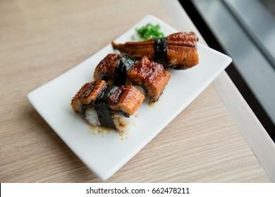 Sushi Nigiri, Unagi, Smoked Eel 3 Piece on white plate