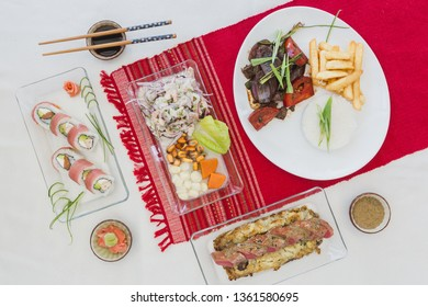 Sushi nikkei, lomo saltado, tuna, ceviche and soy sauce on a white table