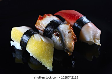Sushi on the black background, close-up, shallow focus