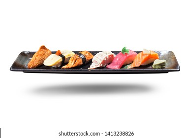 Sushi on black plate. Traditional Japanese dish of prepared vinegared rice, accompanying a variety of seafood, such as tuna, salmon, crab meat, squid, shrimp. Isolated on white background.