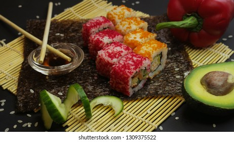 Sushi on a nori seaweed leaf with bell pepper, cucumber and avocado