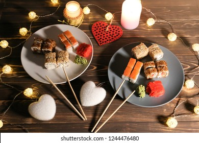 Sushi on the plates with chopsticks on wooden background. Romantic dinner in Japanese style.  Saint Valentines day food. Hearts and candles. Love concept. Salmon, wasabi and ginger. Vegetarian.