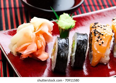 Sushi on the red plate and bowl with soy sauce.