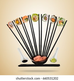 Sushi pieces with chopsticks served on plate, separated on colored background. Many kinds of popular sushi food with chopsticks. Concept of flying asian dish with ingredients