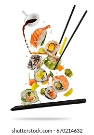 Sushi pieces placed between chopsticks, separated on white background. Popular sushi food. Very high resolution image