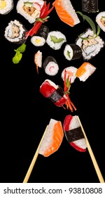 Sushi pieces with sticks flying on black background