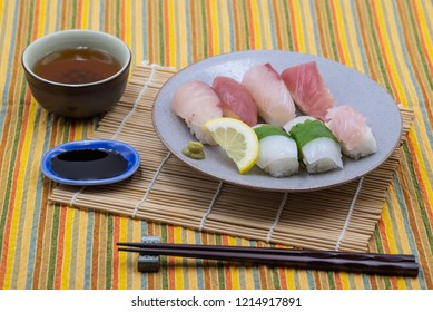 sushi plate with lemon slice, wasabi and soy sauce on bamboo set and colorful tablecloth