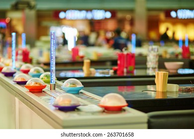 Sushi plates on rails in Japanese restaurant, motion blur