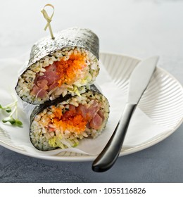 Sushi or poke burrito with nori sheet, raw tuna and vegetables
