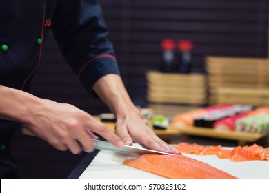 Sushi preparation, making in process, close up on chef hands with knife and salmon