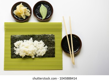 sushi rice on seaweed sit on suchi mat beside chopsticks, ginger, and wasabi on white background