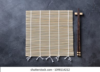 Sushi roll bamboo mat with chopsticks. Top view. Copy space. Grey background.