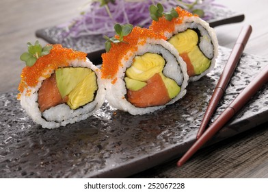Sushi roll : California roll sushi with caviar and chopsticks on black plate