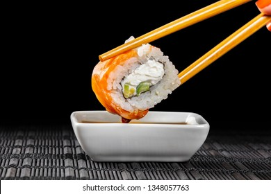 sushi roll dipped in soy sauce on a black background