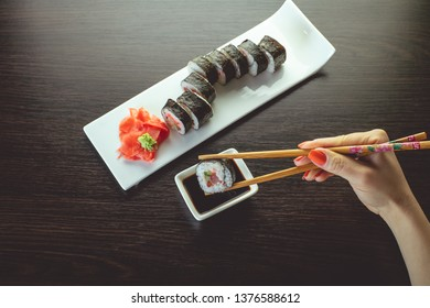 sushi roll dipped in soy sauce closeup