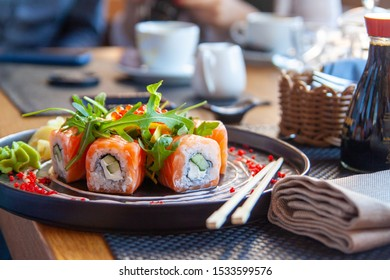 Sushi roll japanese food in restaurant. California Sushi roll set with salmon, vegetables, flying fish roe. Sushi with chopsticks. Japan restaurant menu cuisine.