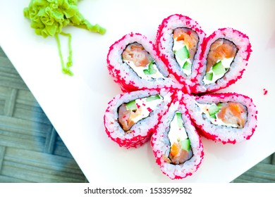 Sushi roll japanese food in restaurant. California Sushi roll set with salmon, vegetables, red flying fish roe. Sushi close up on white plate. Japan restaurant menu cuisine.