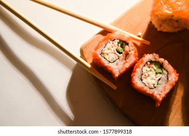 Sushi roll japanese food in restaurant. California Sushi roll set with salmon, vegetables, red flying fish roe. Sushi with chopsticks. Top view. Copyspase. Japan restaurant menu cuisine. Wood board