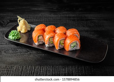 Sushi roll (Philadelphia) with salmon, smoked eel, avocado, cream cheese on black background. Sushi menu. Japanese food.