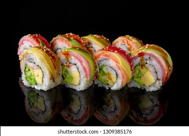Sushi roll (Rainbow) with tuna, salmon, smoked coal, avocado, shrimp, egg omelette, cucumber and avocado on black background. Sushi menu. Japanese food.