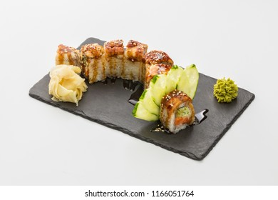 sushi roll of red dragon in black stone plate isolated on white background.