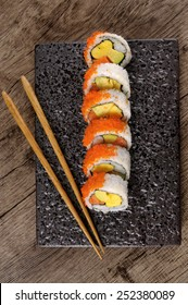 Sushi roll : Row of California roll sushi with caviar and chopsticks on black plate. Top view. Vertical format.