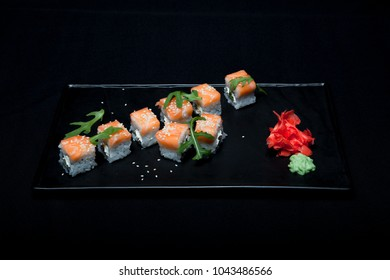 Sushi roll with salmon and avocado on plate on black background top view