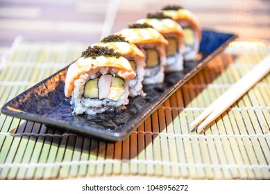 Sushi roll with salmon and crab stick.