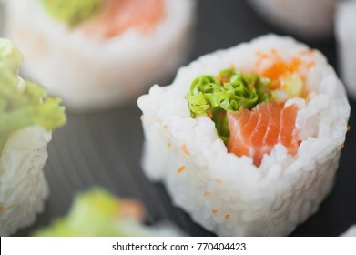 Sushi roll with salmon, lettuce and avocado on the black table