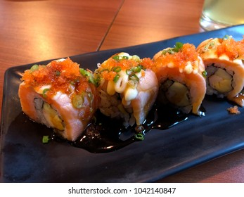 Sushi roll with salmon on black plate