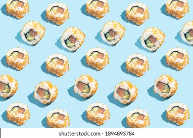 Sushi roll with salmon and tobiko on blue background, food pattern in hard light