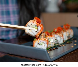 Sushi roll with salmon,Hand holding chopsticks with salmon roll topping with sweet sauce,Traditional Japanese seafood sushi roll,Japanese food,Fresh Sashimi,Fresh salmon,Eating salmon sushi,